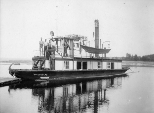 Several men pose for the camera on the upper and lower decks of the William Douglas tug boat.