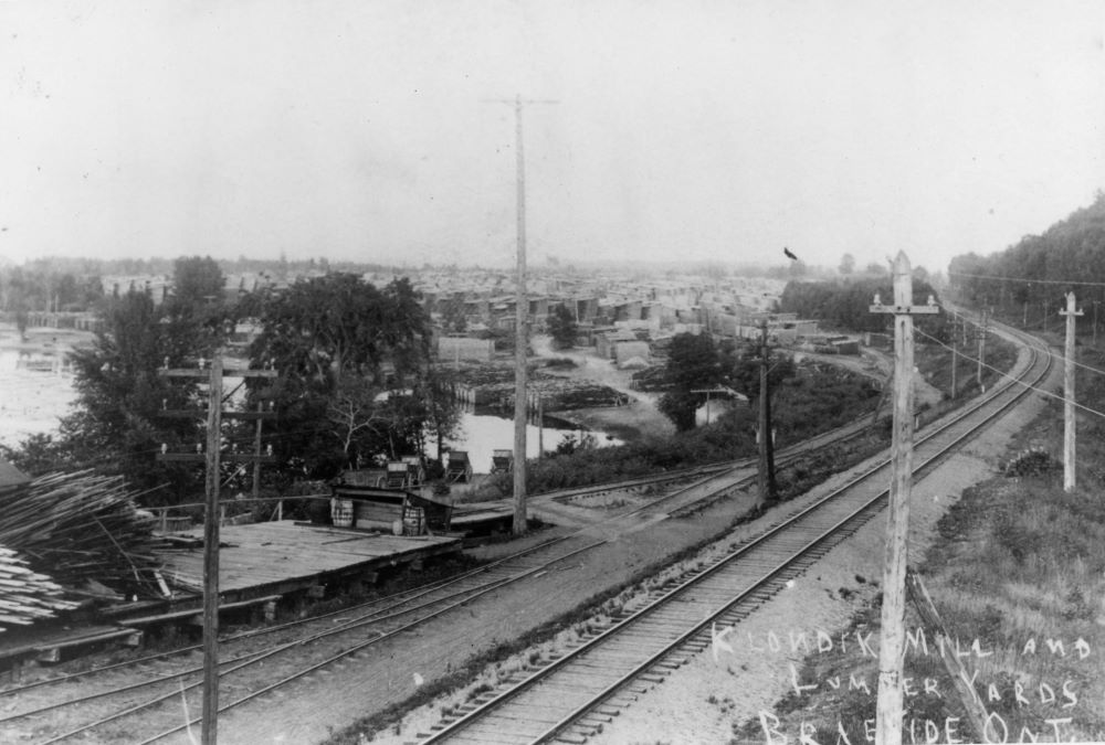 Black and white postcard showing railway tracks running beside a bay with piles of lumber in the distance.