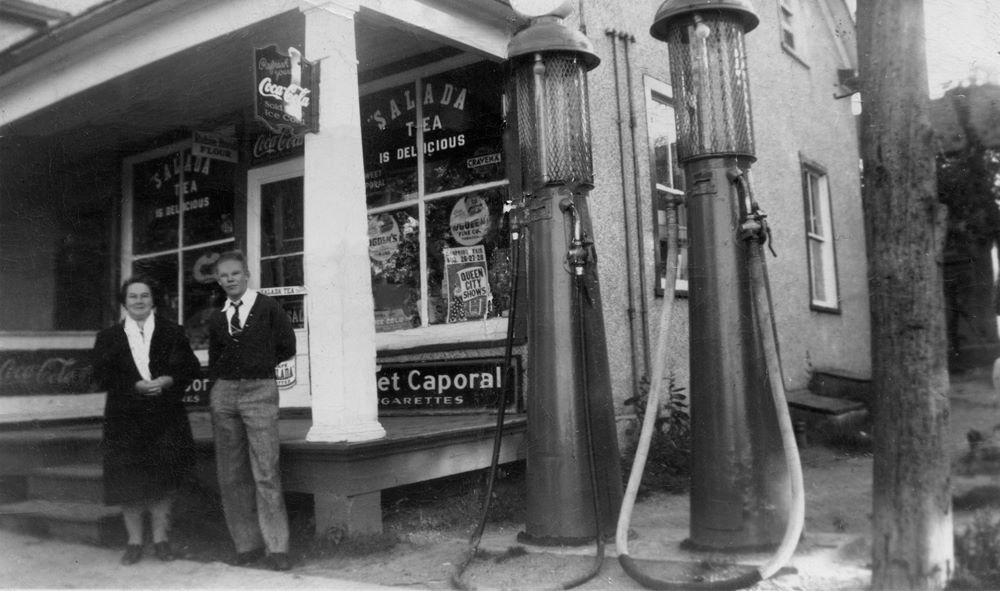 A woman and a young man stand next to old fashioned fuel pumps outside a general store.