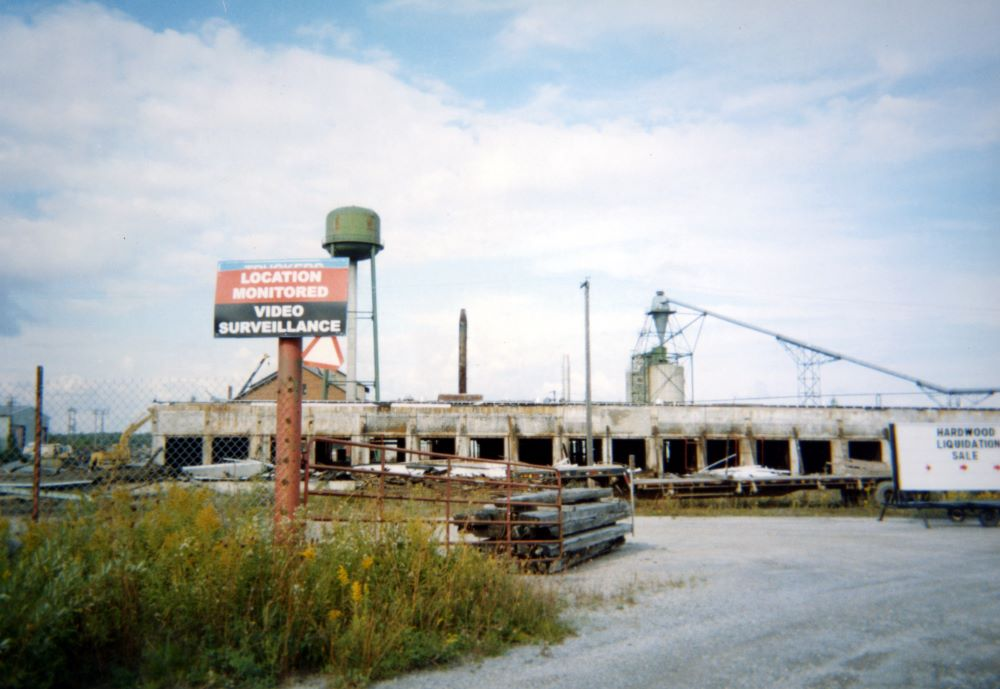 A sign at the entrance to a deserted mill site warns that the location is monitored by video surveillance.
