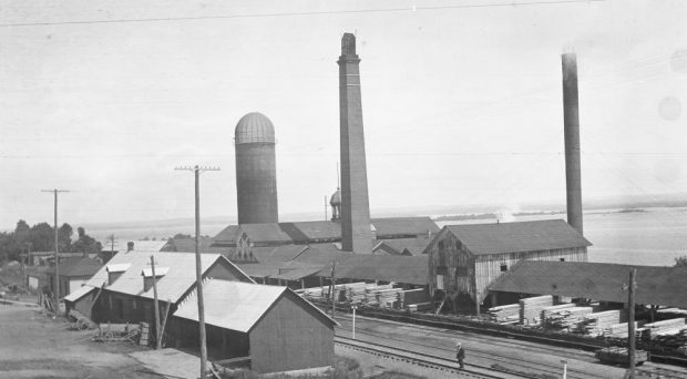 A man stands on a railway track that runs between buildings at a large saw mill site.