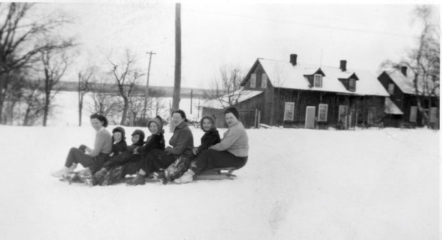 Smiling women and children sit on a long toboggan at the top of a hill.