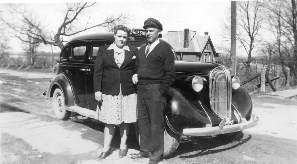 A couple stand on the sidewalk beside a Braeside Taxi car.