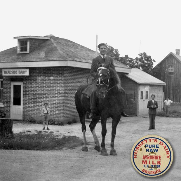 A young man sits on a horse in front of a small building with a sign for the Braeside Dairy over the door. A small boy and two other men look towards the camera. An insert appears in the lower right corner showing a bottle top for Russett's Dairy.