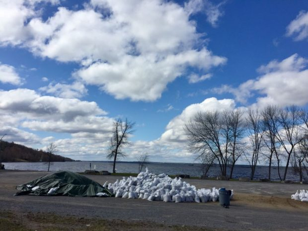 Two large piles of sand bags located in a parking lot near the river are ready for use.