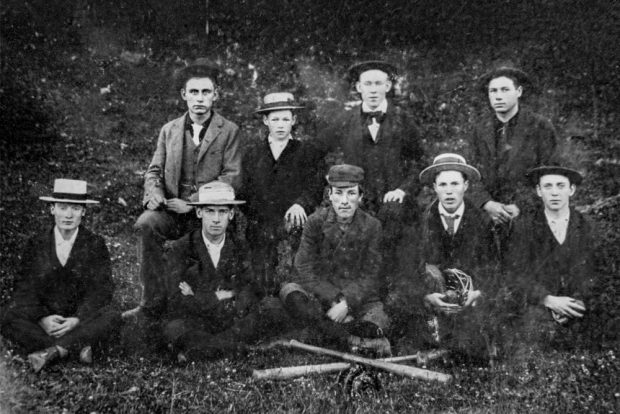 Two rows of baseball players pose for a team photograph in front of crossed wooden bats.