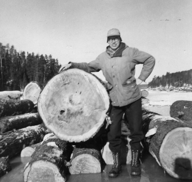 A forester stands on the ice with one hand on his hip and the other draped over a large log.