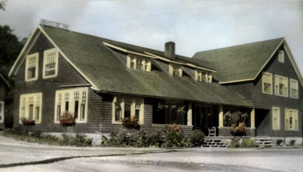 A colour tinted post card shows a large inn with a covered porch and window boxes.