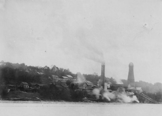 Several buildings surround a mill site on the side of a hill. Steam and smoke from the lake blow off the lake.