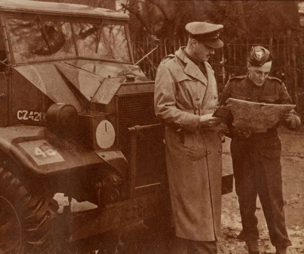 Magazine clipping showing two men in WWII uniforms stand in front of an army tank looking at a map.