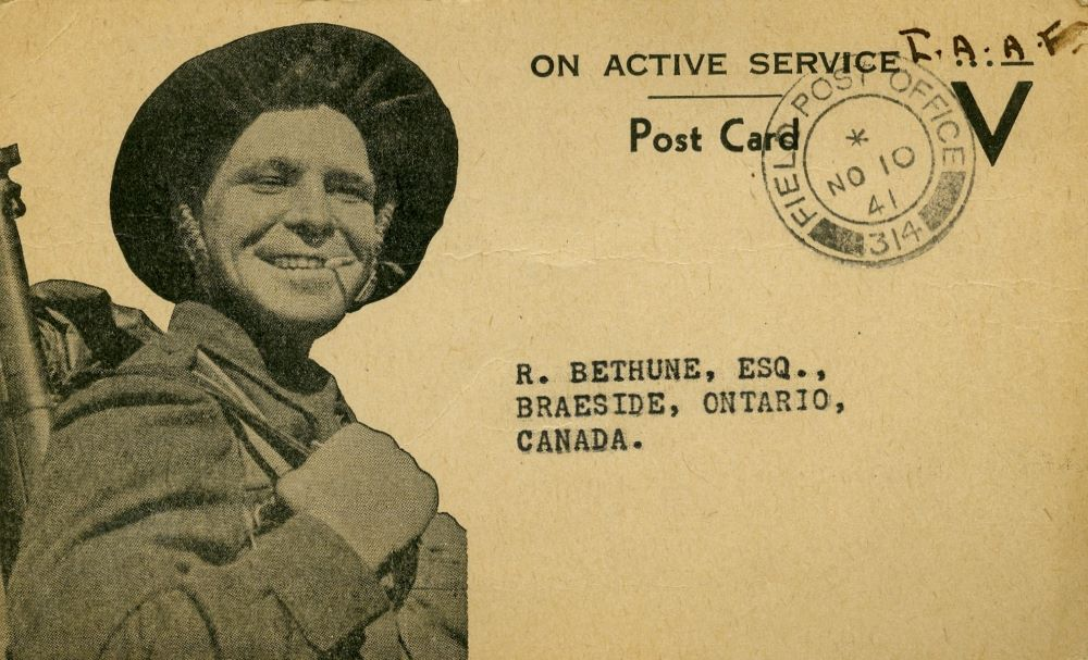 A WWII soldier grinning with a cigarette in his mouth illustrates the front of a stamped post card addressed to R. Bethune, Esquire, Braeside, Ontario, Canada.