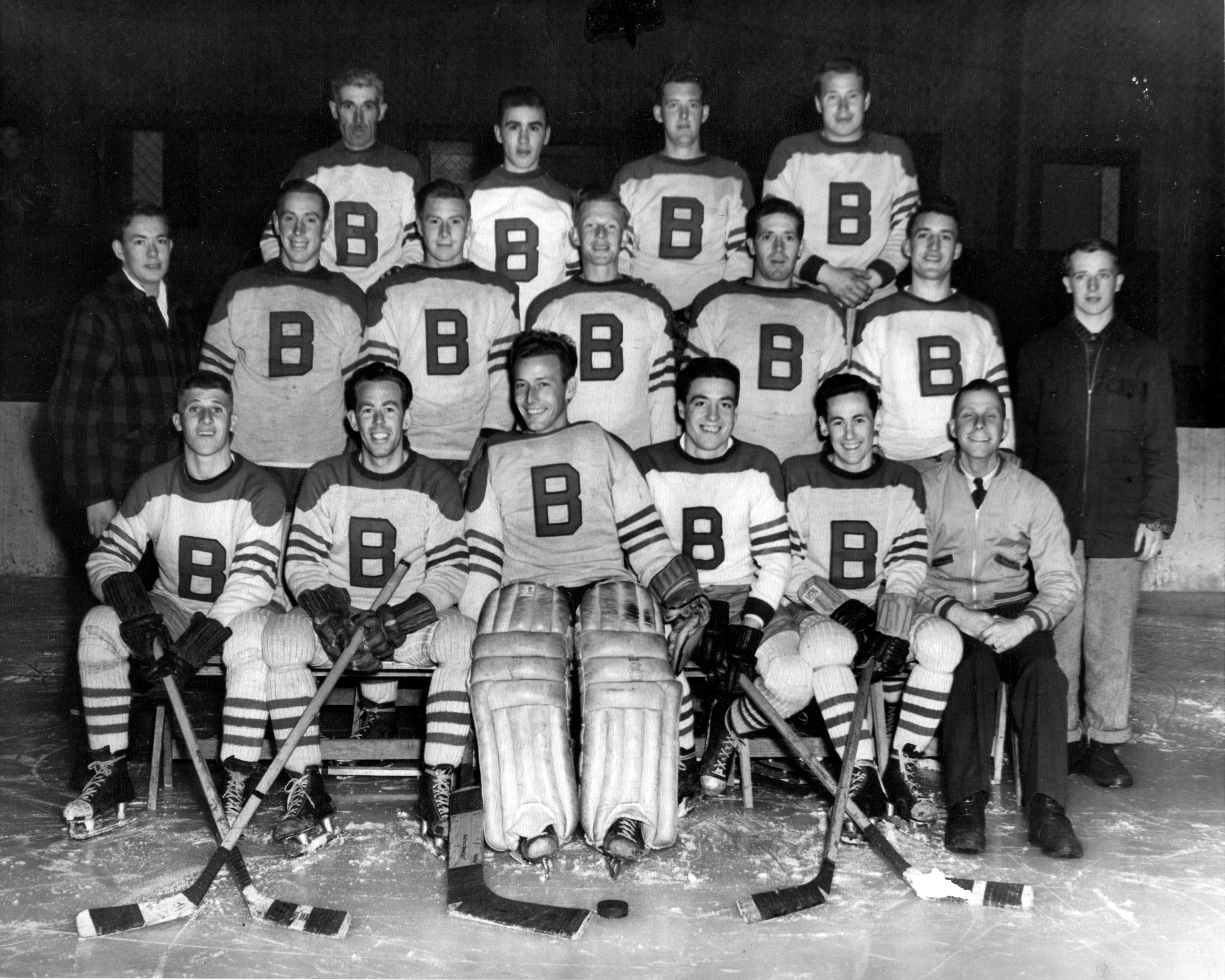 Hockey team photograph shows coaches players wearing white team jerseys with a large B on the front.