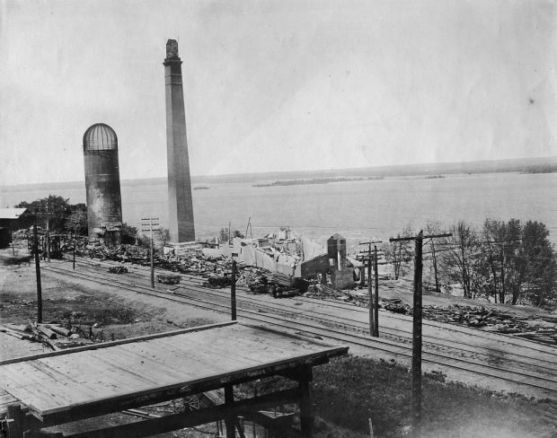 Two chimneys stand among the ruins of burned out buildings next to a river.