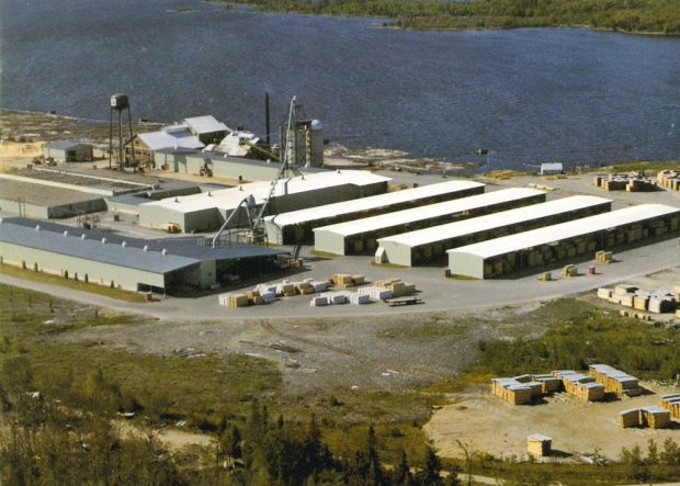 An aerial photograph shows Gillies Bros. mill site in summertime with log booms near shore.