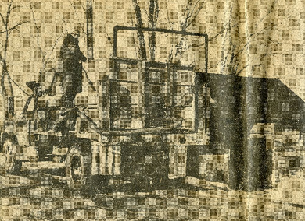 Newspaper clipping shows a man standing on the side of a truck while water is being pumped in from a pipe above.