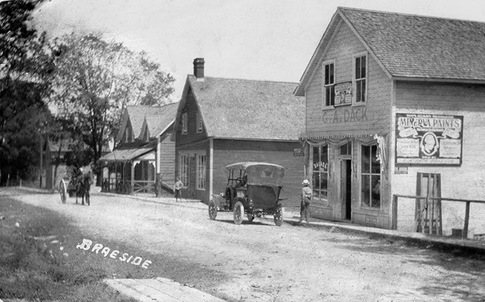 Post card of Braeside shows village street scene with people, stores, a horse drawn carriage an early automobile.