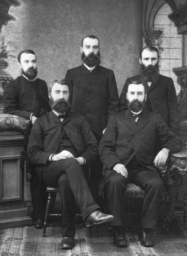 A studio portrait shows three gentlemen standing behind two others who are seated.