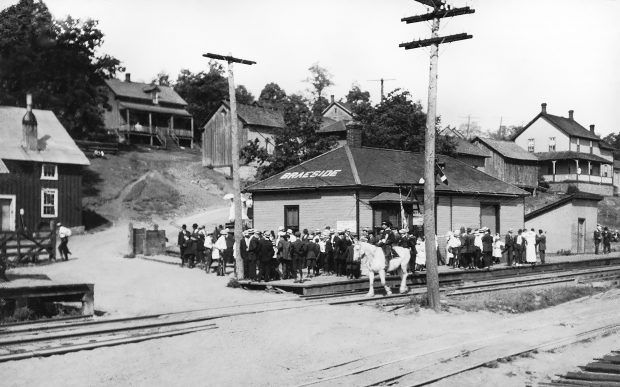 A crowd at the Braeside Train Station watches an Orangeman's Parade led by a man on a white horse.