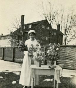 Une jeune femme souriante en uniforme d'infirmière tient un bouquet. Elle est dehors, et près d'elle se trouve une table avec des vases et un rouleau de papier avec ruban.