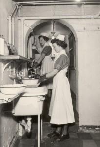 Deux femmes en uniforme d'infirmière portant des gants et faisant du nettoyage devant une série d'éviers.