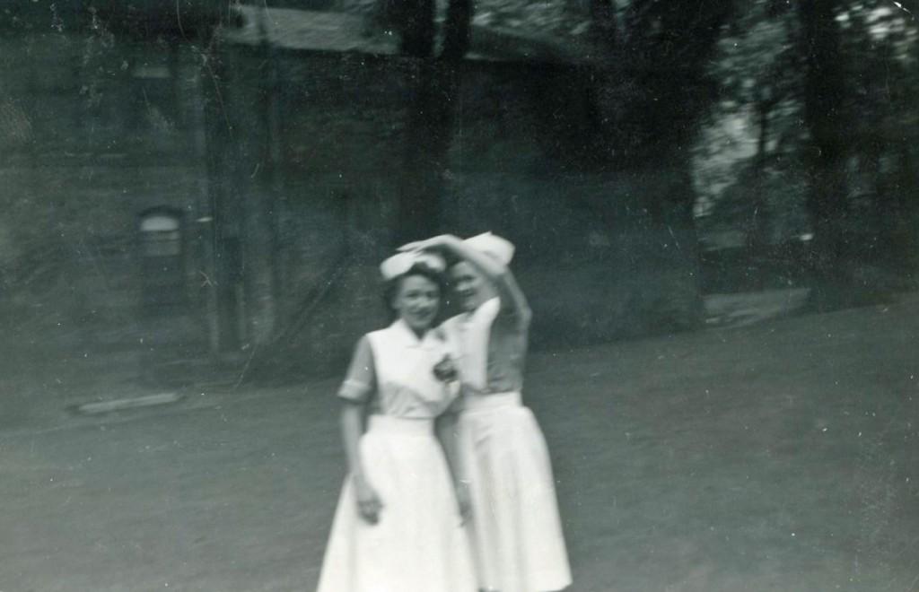Deux femmes souriantes dehors, en uniforme d'infirmière.