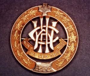 Épingle circulaire, bordée de feuilles et couronnée d'une croix. Les lettres W, C et H sont entrelacées au-dessus de la devise.