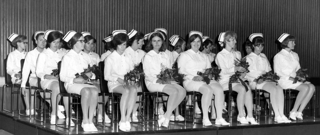 Over 20 women sit on a stage in full nurses' uniforms, holding flowers.