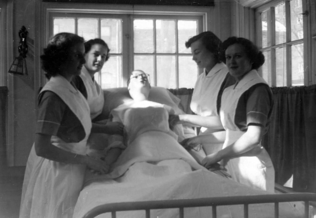 Quatre femmes en uniforme d'infirmière sans coiffe entourent un lit et tiennent un mannequin.