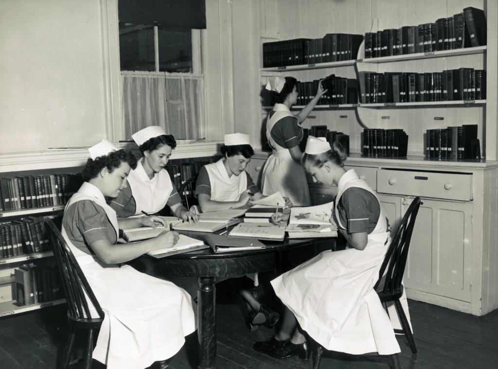 Quatre femmes assises à une table couverte de livres. Une cinquième tend la main vers une étagère.