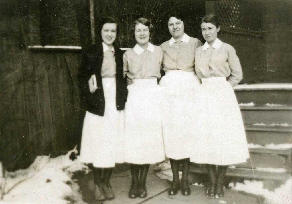 Quatre femmes souriantes portent de longues jupes blanches et des chemisiers légers.