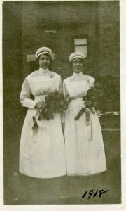 Deux femmes en uniforme d'infirmière se tiennent devant un immeuble de briques, tenant des bouquets et souriant.