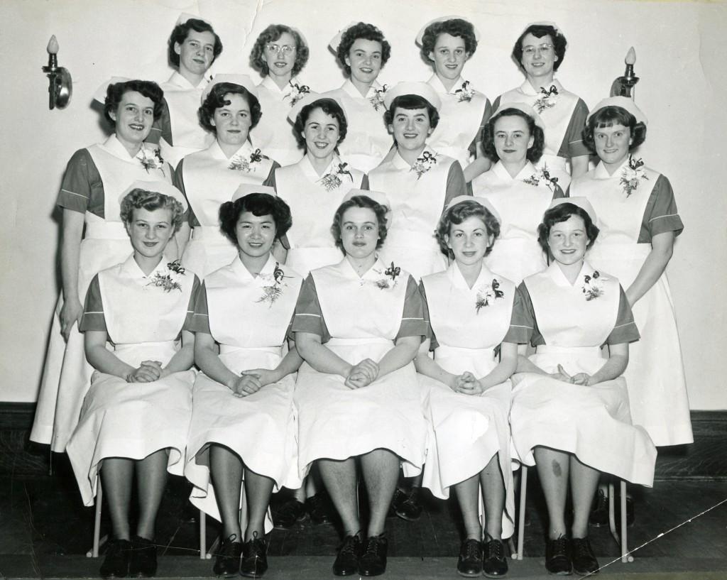 Seize femmes souriantes en uniforme d'infirmière assises ou debout pour une photo officielle.