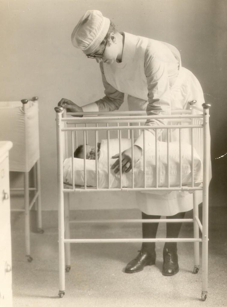 Une jeune femme se penche sur un berceau où se trouve un bébé. Elle porte un uniforme d'infirmière.