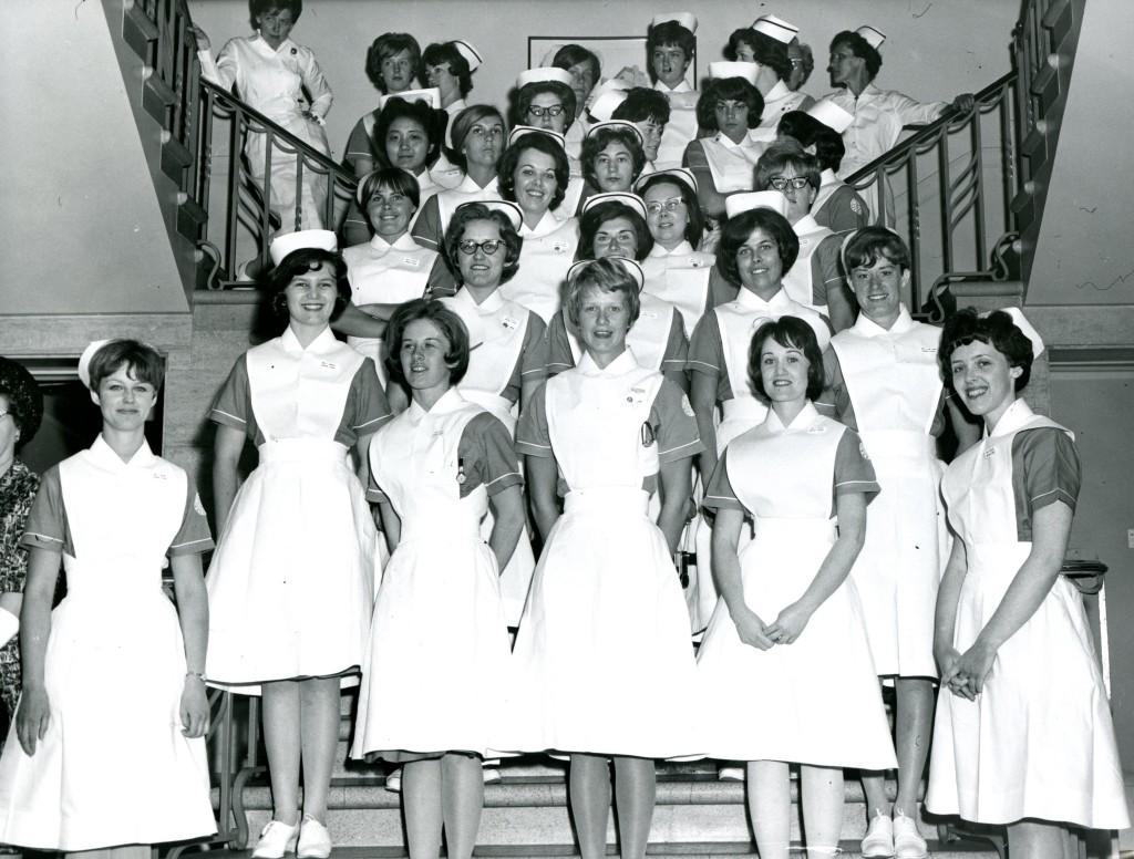 Un grand groupe de femmes pose pour un photographe sur un escalier. Elles portent des uniformes d'infirmière avec coiffes.