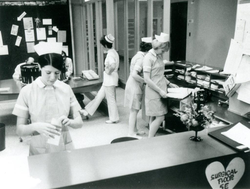 Six personnes parlent et manipulent des documents dans une aire de réception. Quatre femmes portent une cape d'infirmière.