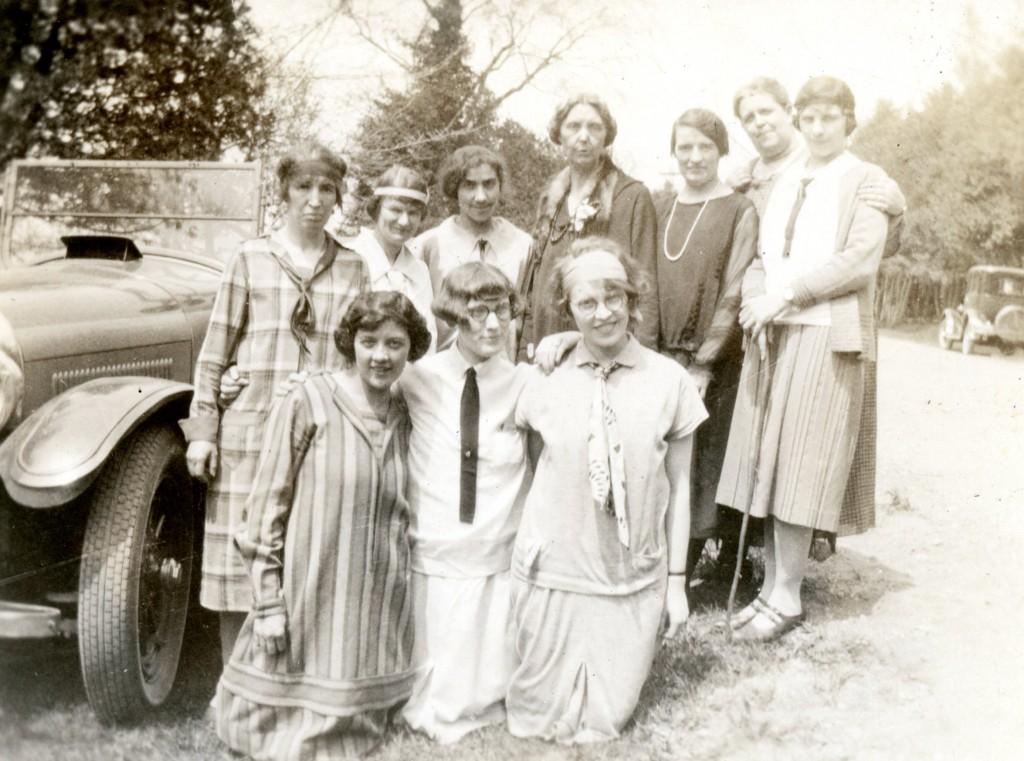 Dix femmes habillées de façon décontractée posent à côté d'un véhicule motorisé un jour ensoleillé. Il y a des arbres à l'arrière-plan.
