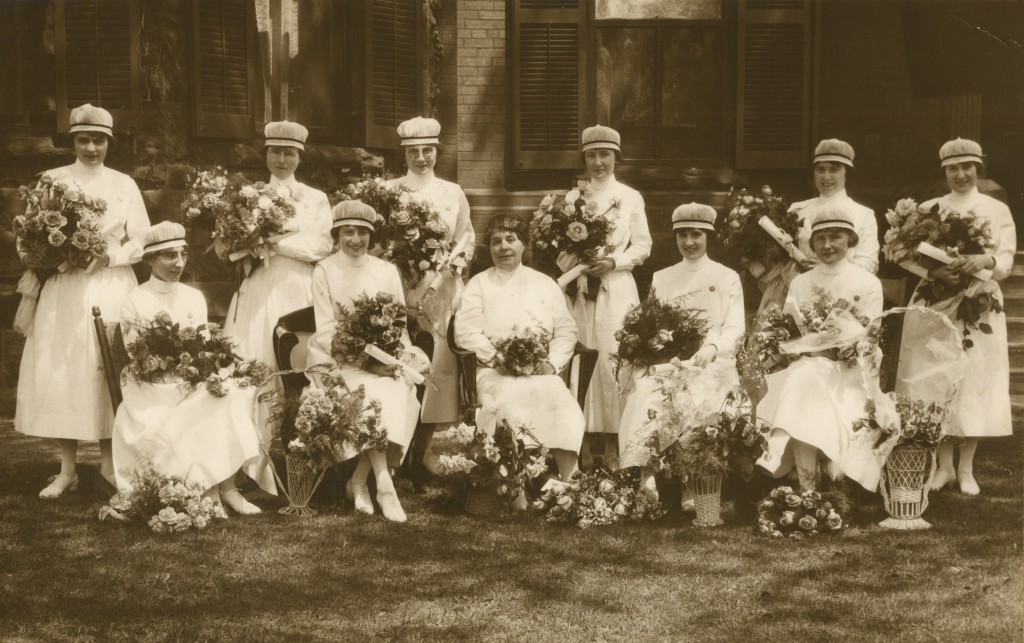 Onze femmes souriantes posent officiellement avec des bouquets de fleurs. Toutes les femmes sauf une portent une coiffe d'infirmière.