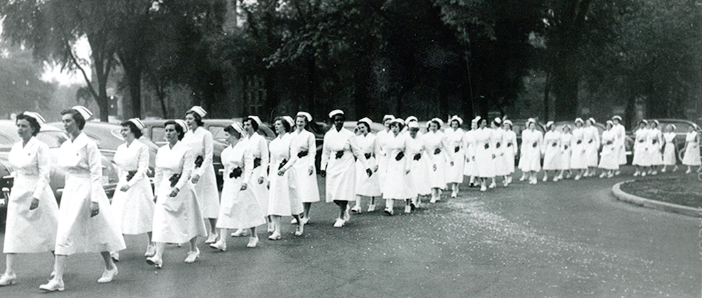 Over 30 women march in a row, wearing white uniforms, caps, and shoes.