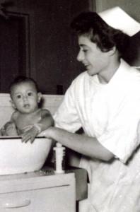 Une jeune femme souriante, portant uniforme et coiffe d'infirmière, donne un bain à un bébé dans une cuvette.