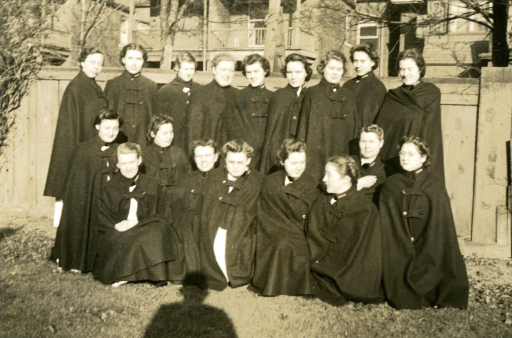 Dix-huit jeunes femmes posent pour une photo. Elles portent des capes d'infirmière fermées et sont dehors devant une clotûre. On peut voir l'ombre du photographe au sol.