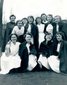 Twelve young women smile as they pose for the camera. They are outside, and most are wearing nurse's capes over their uniforms.