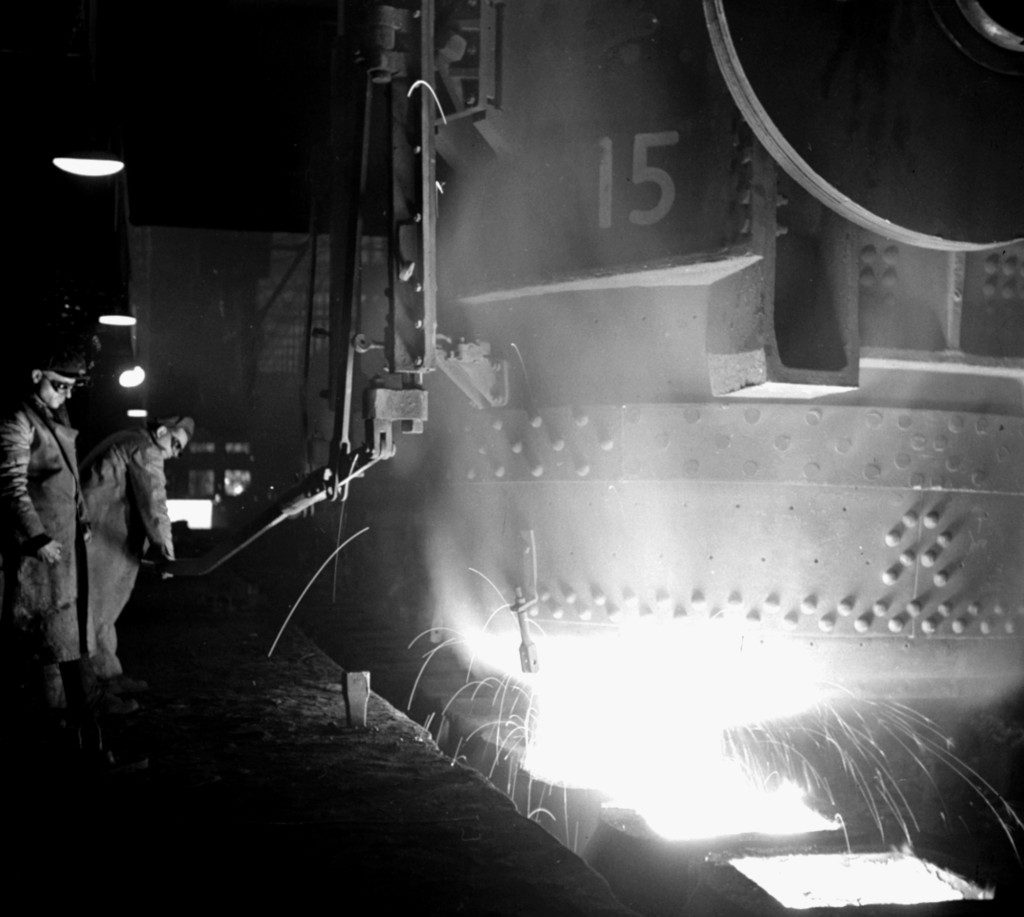 Two workers pouring molten steel in an industrial steel mill