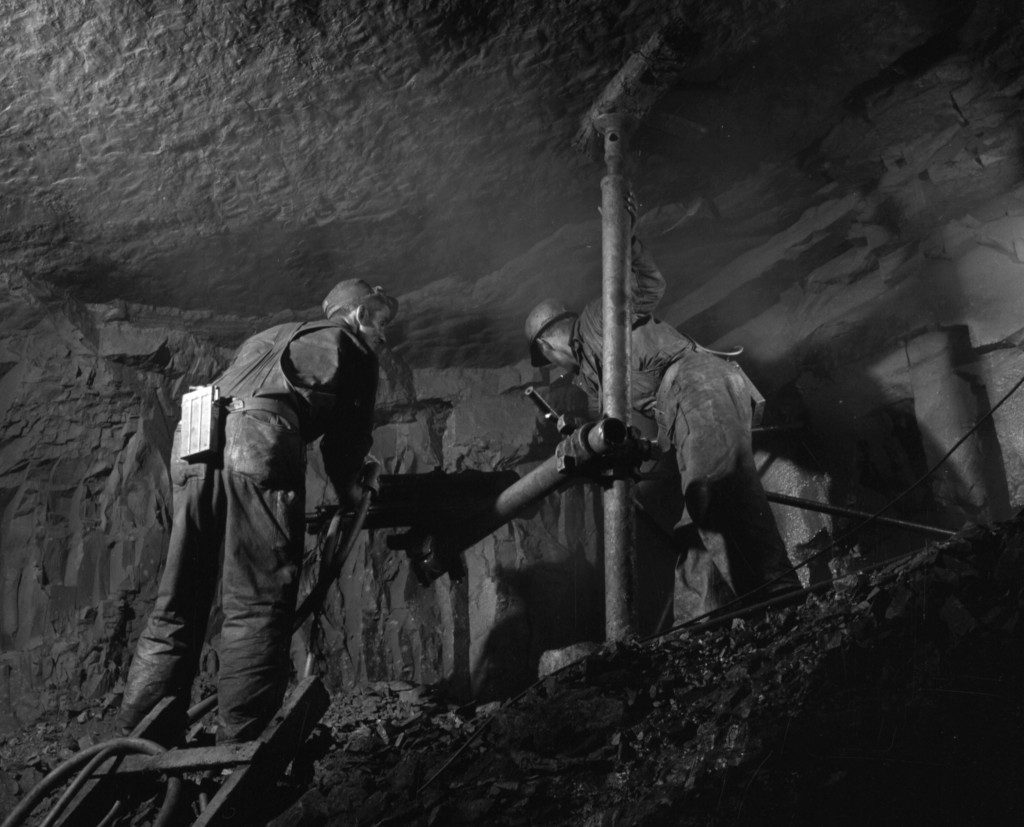 two workers operating a rock drill in a mine shaft at Bell Island