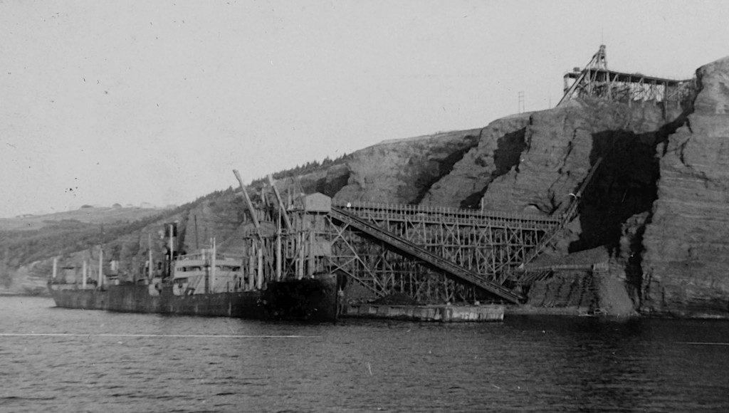 old photo of a cargo ship tied up at a loading pier with a conveyor belt