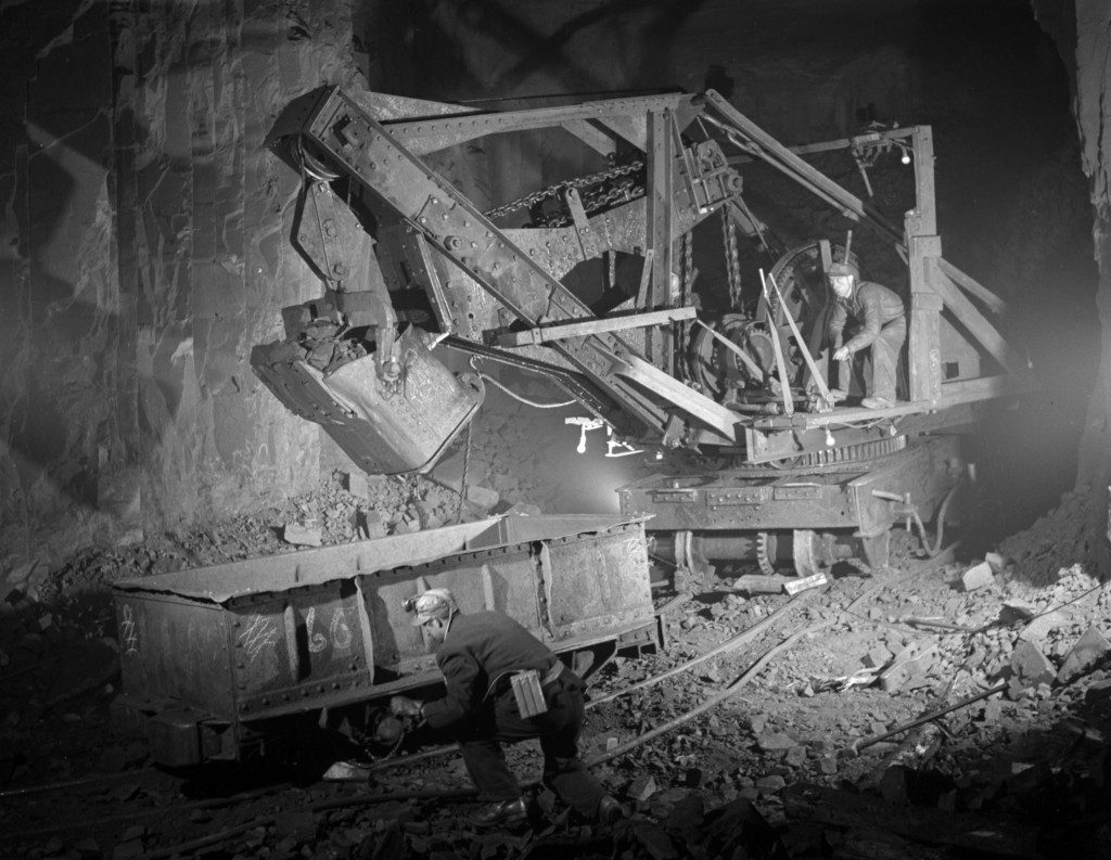 Power shovel loading iron ore into an ore car and two workers in a mine shaft