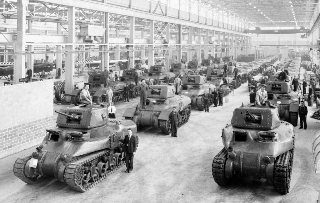 three rows of dozens of army tanks and workers in a factory