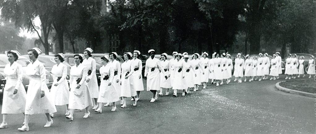 Over 30 women march in a row, wearing white uniforms, caps, and shoes. - Plus de 30 femmes marchent en rangée, portant uniforme, coiffe et souliers blancs.