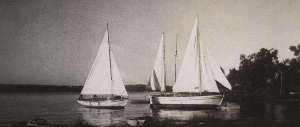 Black and white photograph of three white yachts, with hoisted sails, anchored near the shore. -Photographie noir et blanc de trois yachts blancs, aux voiles hissées, ancrés près de la rive.