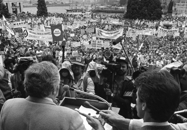 A man, speaking at a podium, faces out towards a large crowd of people on the lawn of the B.C. legislature. Reporters are gathered, holding microphones and cameras towards the podium. Organizational banners and protest signs are visible throughout the crowd.
