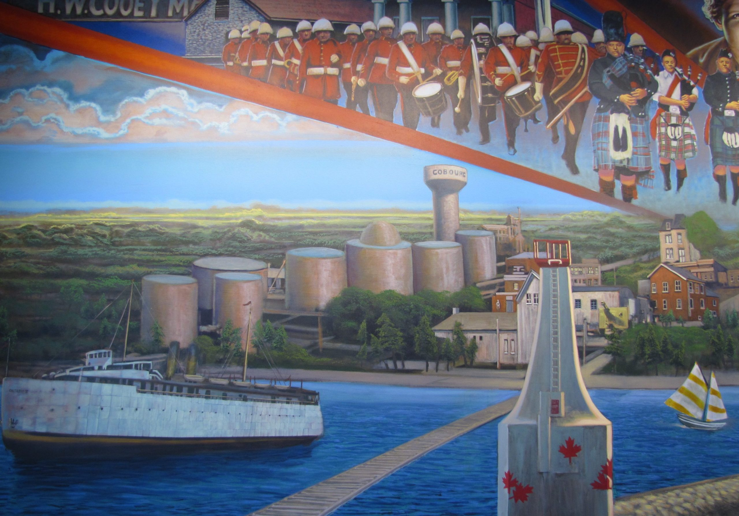 A colourful mural showing the current white Cobourg lighthouse to the right and a large white ferry to the left. On shore, in the distance to the left and centre, are seven large silver oil tanks and a water tower, and to the right beyond the lighthouse are a few businesses . Above them are depicted the red uniformed Cobourg Concert Band in marching formation and the Legion Bagpipe band in varied kilts.